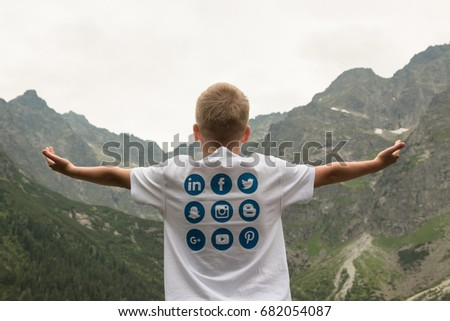 Krakow, Poland - July, 2017:Boy teenager in a T-shirt with logos of social networks Twitter, Facebook, Snapchat, Instagram, Blogger, Linkedin. The background of mountains. Concept. Travels. Traveler.