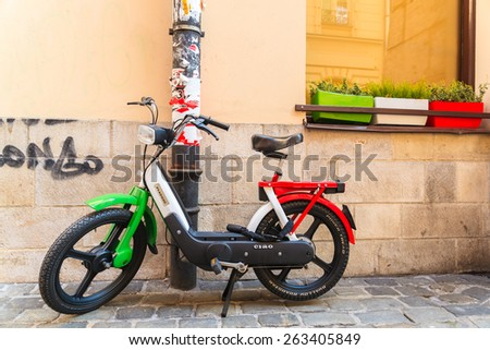KRAKOW, POLAND - MAR 24, 2015: old Italian scooter parked on street of Krakow city in front of restaurant. Krakow is most visited tourist destination in Poland - stock photo
