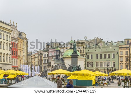 KRAKOW, POLAND - MARCH 5, 2014: Unidentified tourists taking a walk at Main Square (Rynek Glowny). It dates to the 13th century, and at roughly 40,000 m2 - largest medieval town square in Europe.