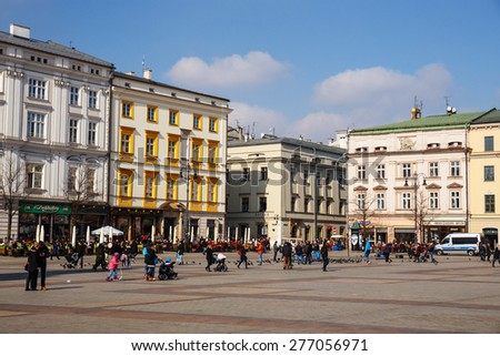 KRAKOW, POLAND - March 07 2015: Unidentified tourists visiting main market square in Krakow, Poland on March 07 2015. Old town of Cracow listed as unesco heritage site
