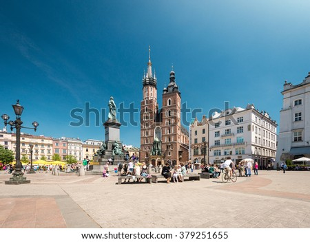Krakow, Poland - May 16, 2013. Tourists visiting main market square in front of St. Mary's Basilica, in Krakow, Poland, Europe. Old medieval  town of Cracow listed as unesco heritage site. - stock photo