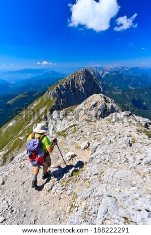 KRANJSKA GORA, SLOVENIA - AUGUST 18th 2013: Mountaineer walking on the ridge of the Mojstrovka mountain in Julian Alps on a fine summer day. - stock photo