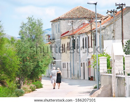 Krapanj island, Riviera Sibenik, Croatia - June 27, 2009. Two elderly people walking in a old street of Krapanj, a medieval small island of the Adriatic sea. Summer day. Travel concept. - stock photo