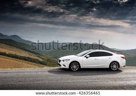 Krasnodar, Russia - September 07, 2014: White Car Mazda 6 parket at countryside asphalt road near green mountains at daytime