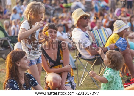 """Krasnoyarsk, Russia - June 19: Children playing with soap bubbles during  watching Summer Youth Festival of symphonic music """"Band on the grass"""" on the island Tatyshev - stock photo"""