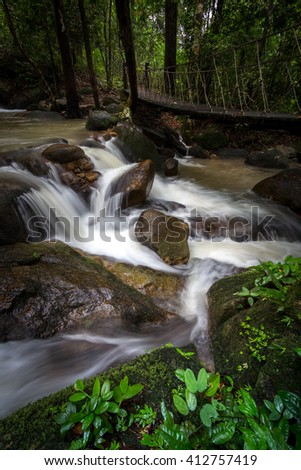 Krating waterfall in tropical forest with rope bridge and plant - stock photo