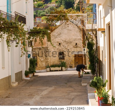 Kritsa, Greece - September 13, 2014: Women working in front of the house in town of Kritsa. It is one of the oldest and most picturesque villages in Crete, Greece,  at an altitude of 375 m.
