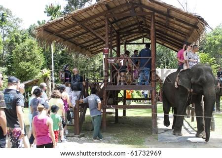 KUALA GANDAH, MALAYSIA - SEPTEMBER 25 : Visitors to Kuala Gandah Elephant Orphanage Sanctuary line-up for elephant ride during Elephant Awareness Program September 25 2010 in Kuala Gandah, Malaysia. - stock photo