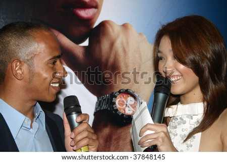 KUALA LUMPUR - APRIL 4: British F1 driver Lewis Hamilton being interviewed by Malaysian celebrity Marion Caunter at the 2007 TAG Heuer F1 Street Party April 4, 2007 in Kuala Lumpur, Malaysia. - stock photo