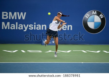 KUALA LUMPUR - APRIL 20, 2014: Chan Hao-Ching of Taiwan returns at the doubles final of the BMW Malaysian Open Tennis in Kuala Lumpur, Malaysia. She partners Timea Babos of Hungary to emerge winners. - stock photo