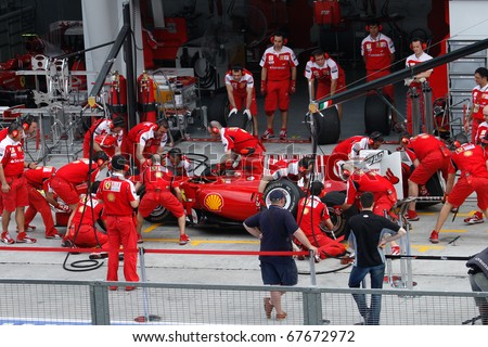 KUALA LUMPUR - APRIL 2: Ferrari pit-crew practices tire change on practice day at the 2010 Petronas Malaysia F1 Grand-Prix on April 2, 2010 in Sepang, Malaysia. - stock photo
