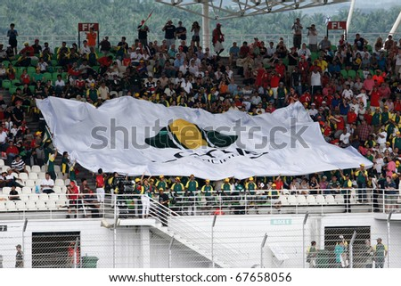 KUALA LUMPUR - APRIL 4: Lotus team supporters unfurl huge Lotus team flag on the terraces on race day at the 2010 Petronas Malaysia Grand-Prix on April 4, 2010 in Sepang International Circuit. - stock photo