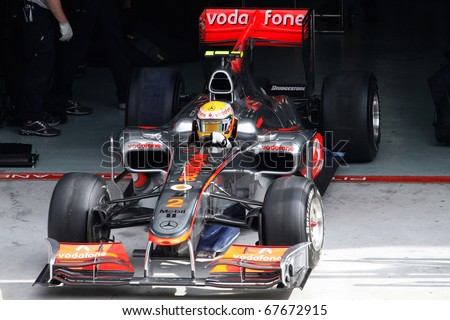 KUALA LUMPUR - APRIL 2: McLaren's driver Lewis Hamilton exits the garage for his practice lap on practice day at the 2010 Petronas Malaysia F1 Grand-Prix on April 2, 2010 in Sepang, Malaysia. - stock photo