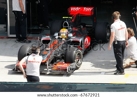 KUALA LUMPUR - APRIL 2: McLaren's driver Lewis Hamilton prepares to take to the tracks on practice day at the 2010 Petronas Malaysia F1 Grand-Prix on April 2, 2010 in Sepang, Malaysia. - stock photo