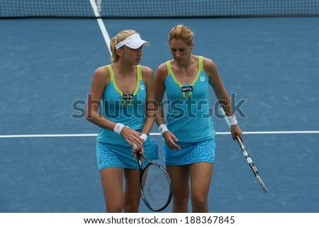 KUALA LUMPUR - APRIL 19, 2014: Olga Savchuk and Lyudmyla Kichenok (white cap) discus tactics in between service in the women's semifinals of the BMW Malaysian Open tennis is Kuala Lumpur, Malaysia. - stock photo