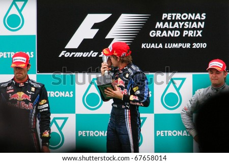 KUALA LUMPUR - APRIL 4: Race winner Sebastian Vettel of the Red Bull team kisses the trophy he won at the 2010 Petronas Malaysia GP on April 4, 2010 in Sepang. Vettel went on to become world champion. - stock photo