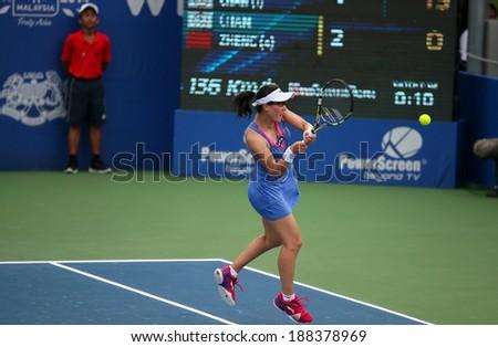 KUALA LUMPUR - APRIL 20, 2014: Zheng Saisai of China returns at the doubles final of the BMW Malaysian Open Tennis in Kuala Lumpur, Malaysia. She partners Chan Yung-Jan of Taiwan to emerge runners-up. - stock photo