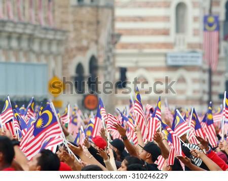 KUALA LUMPUR - Aug 27 : Crowd waving Malaysian Jalur Gemilang flag during the rehearsal for National Day parade on Aug 27,2015 at Bangunan Sultan Abdul Samad ,Dataran Merdeka, Kuala Lumpur, Malaysia - stock photo