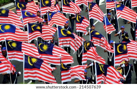 KUALA LUMPUR - AUGUST 31: Youth carrying the flag of malaysia during 57th Celebrations, Malaysian Independence Day Parade on August 31, 2014 in Kuala Lumpur, Malaysia.  - stock photo