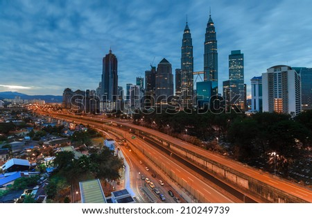 Kuala Lumpur city during blue hour with heavy clouds. - stock photo