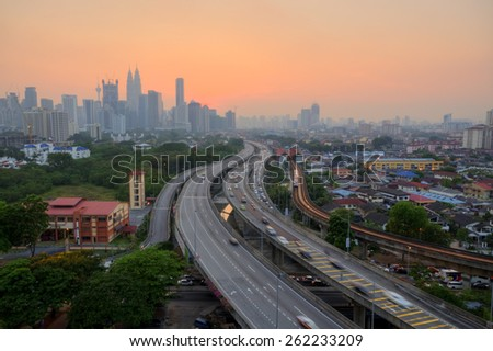 Kuala Lumpur City skyline at sunset Image has grain or blurry or noise and soft focus when view at full resolution. (Shallow DOF, slight motion blur) - stock photo