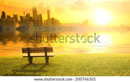 kuala lumpur city sunset view over a bench and a lake - stock photo
