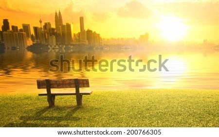 kuala lumpur city sunset view over a bench and a lake - stock photo