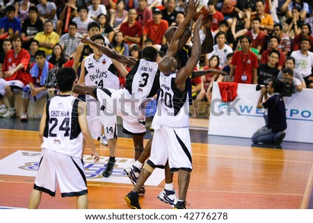 KUALA LUMPUR - DECEMBER 13: KL Dragons' Chris Kuete blocks an attempt by Thailand Tigers' Ikenna Nwankwo in the ASEAN Basketball League match. December 13, 2009 in Kuala Lumpur. - stock photo