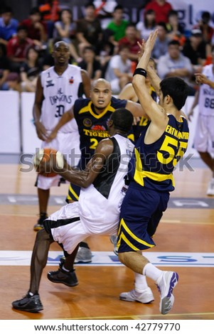 KUALA LUMPUR - DECEMBER 13: KL Dragons' Chris Kuete (C) powers in to score in this match against Thailand Tigers in the ASEAN Basketball League match December 13, 2009 in Kuala Lumpur. - stock photo