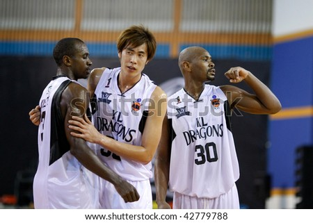 KUALA LUMPUR - DECEMBER 13: KL Dragons' Chris Kuete (L), Li Wei (C) and Jamal Brown celebrating a point against Thailand Tigers in the ASEAN Basketball League game December 13, 2009 in Kuala Lumpur. - stock photo