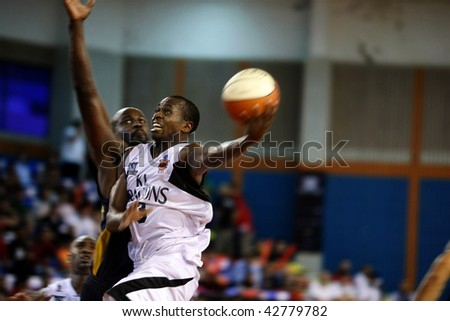 KUALA LUMPUR - DECEMBER 13: KL Dragons' Chris Kuete (R) powers in for a slam-dunk in this match against Thailand Tigers in the ASEAN Basketball League match December 13, 2009 in Kuala Lumpur. - stock photo