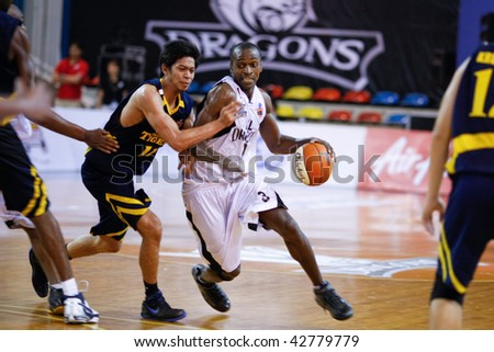 KUALA LUMPUR - DECEMBER 13: KL Dragons' Chris Kuete (R) rushes into the paint in this match against Thailand Tigers in the ASEAN Basketball League match December 13, 2009 in Kuala Lumpur. - stock photo