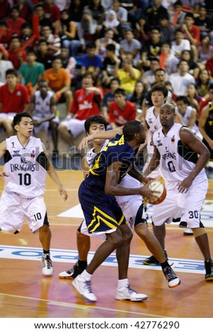 KUALA LUMPUR - DECEMBER 13: KL Dragons defends an attack by Thailand Tigers' Chaz Briggs in the ASEAN Basketball League match. December 13, 2009 in Kuala Lumpur. - stock photo
