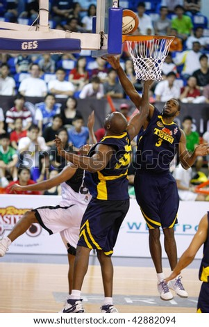 KUALA LUMPUR - DECEMBER 13: KL Dragons' Guga (L) sneaked the ball in between the hands of the Thailand Tigers' I. Nwankwo(C) and C. Briggs (R) in the ABL match on December 13, 2009 in Kuala Lumpur. - stock photo