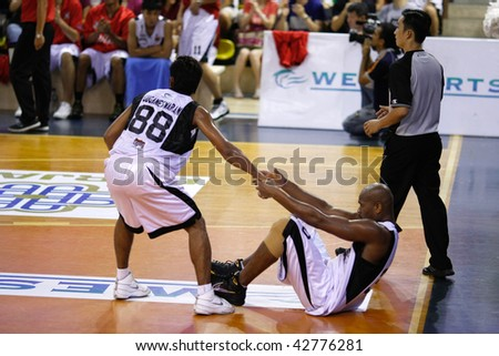 KUALA LUMPUR - DECEMBER 13: KL Dragons' Guganeswaran gives Jamal Brown a helping hand in the ASEAN Basketball League match. December 13, 2009 in Kuala Lumpur. - stock photo