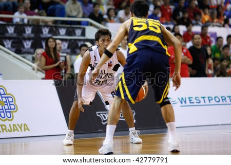 KUALA LUMPUR - DECEMBER 13: KL Dragons' Guganeswaran (L) looks for an opening in this match against Thailand Tigers in the ASEAN Basketball League match December 13, 2009 in Kuala Lumpur. - stock photo