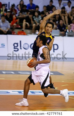 KUALA LUMPUR - DECEMBER 13: KL Dragons' Guganeswaran runs in for a lay-up against Thailand Tigers in the ASEAN Basketball League match December 13, 2009 in Kuala Lumpur. - stock photo