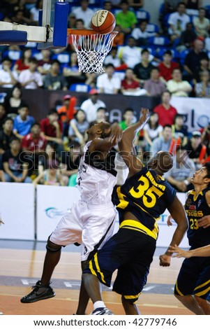 KUALA LUMPUR - DECEMBER 13: KL Dragons' Jamal Brown (L) and Thailand Tigers' Ikenna Nwankwo jumps for a rebound in the ASEAN Basketball League match December 13, 2009 in Kuala Lumpur. - stock photo