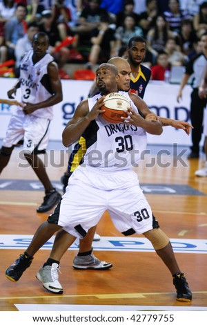 KUALA LUMPUR - DECEMBER 13: KL Dragons' Jamal Brown (#30) looks towards the hoop in this match against Thailand Tigers in the ASEAN Basketball League match December 13, 2009 in Kuala Lumpur. - stock photo