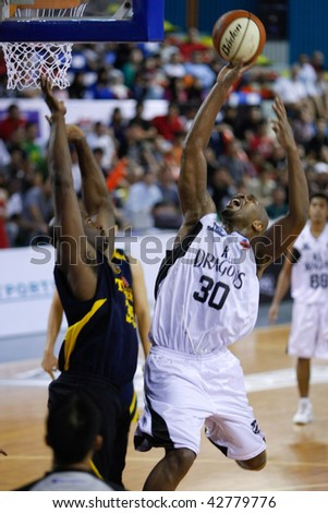 KUALA LUMPUR - DECEMBER 13: KL Dragons' Jamal Brown (R) in a fade-away jumper, in this match against Thailand Tigers in the ASEAN Basketball League match December 13, 2009 in Kuala Lumpur. - stock photo
