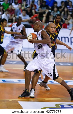 KUALA LUMPUR - DECEMBER 13: KL Dragons' Jamal Brown (#30) turns around Thailand Tigers' Chaiwat Kaedum to score in the ASEAN Basketball League match December 13, 2009 in Kuala Lumpur. - stock photo