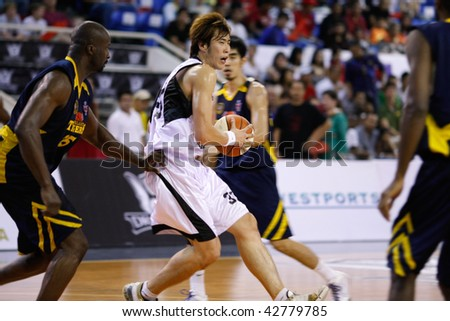 KUALA LUMPUR - DECEMBER 13: KL Dragons' Li Wei (2nd L) shields the ball against Thailand Tigers' Ikenna Kwankwo in the ASEAN Basketball League match December 13, 2009 in Kuala Lumpur. - stock photo