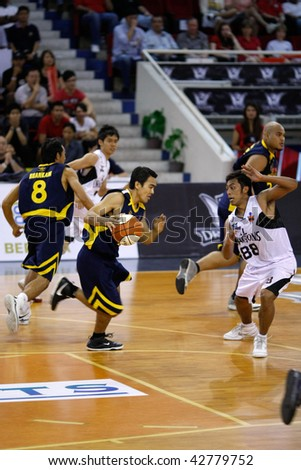 KUALA LUMPUR - DECEMBER 13: Thailand Tigers initiate an attack on KL Dragons in the ASEAN Basketball League match December 13, 2009 in Kuala Lumpur. - stock photo
