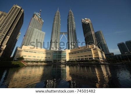 KUALA LUMPUR - FEBRUARY 17: Petronas Twin Towers - tallest twin buildings in the world at the sunrise light with reflection in a pond in Kuala Lumpur on On Februrary 17, 2011. The building is 451,9 m and 88 floors. - stock photo