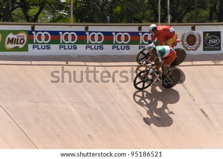 KUALA LUMPUR - FEBRUARY 9: Rider from China (red) competed with rider from Iran (green white) during Asian Cycling Championships 2012 held in Kuala Lumpur, Malaysia on February 9, 2012. - stock photo