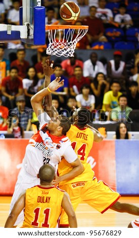 KUALA LUMPUR - FEBRUARY 19:Slingers Donald Little (14) and Dragons Brian Williams (33) rebound for the ball at an ASEAN Basketball League match on February 19, 2012 in Kuala Lumpur, Malaysia.  Dragons won 86-71. - stock photo