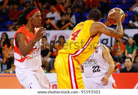 KUALA LUMPUR - FEBRUARY 19: Slingers' Donald Little (14) shields the ball from Tiras Wade of the Dragons at the ASEAN Basketball League match on February 19, 2012 in Kuala Lumpur, Malaysia. Dragons won 86-71. - stock photo