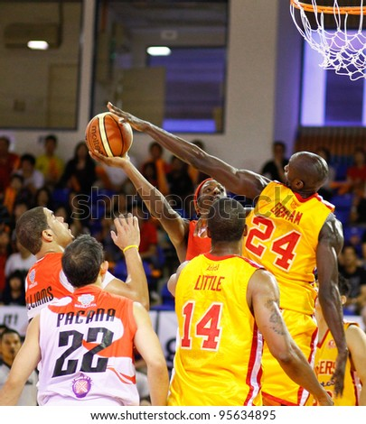 KUALA LUMPUR - FEBRUARY 19: Slingers' Donald Little (14) watches Louis Graham (24) blocks Dragons T. Wade shot at the ASEAN Basketball League match on Feb 19, 2012 in Kuala Lumpur. Dragons won 86-71. - stock photo