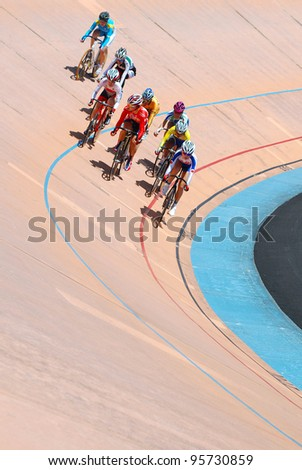 KUALA LUMPUR, FEBRUARY 11: Unidentified female riders from various Asian countries participate in the track event during the Asian Cycling Championships 2012 at the Kuala Lumpur Velodrome, Malaysia on February 11, 2012 - stock photo