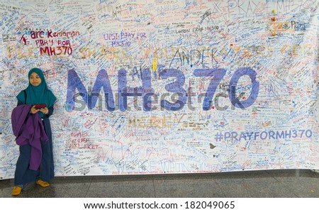 KUALA LUMPUR INTERNATIONAL AIRPORT - MARCH 17: Unidentified Muslim girl poses in front of a banner in support of Malaysia Airlines Boeing 777-200ER MH370 on March 17, 2014 in KLIA, Sepang, Malaysia. - stock photo